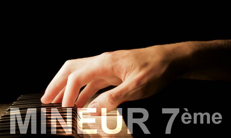 Main sur un piano. Accords de piano mineurs septième